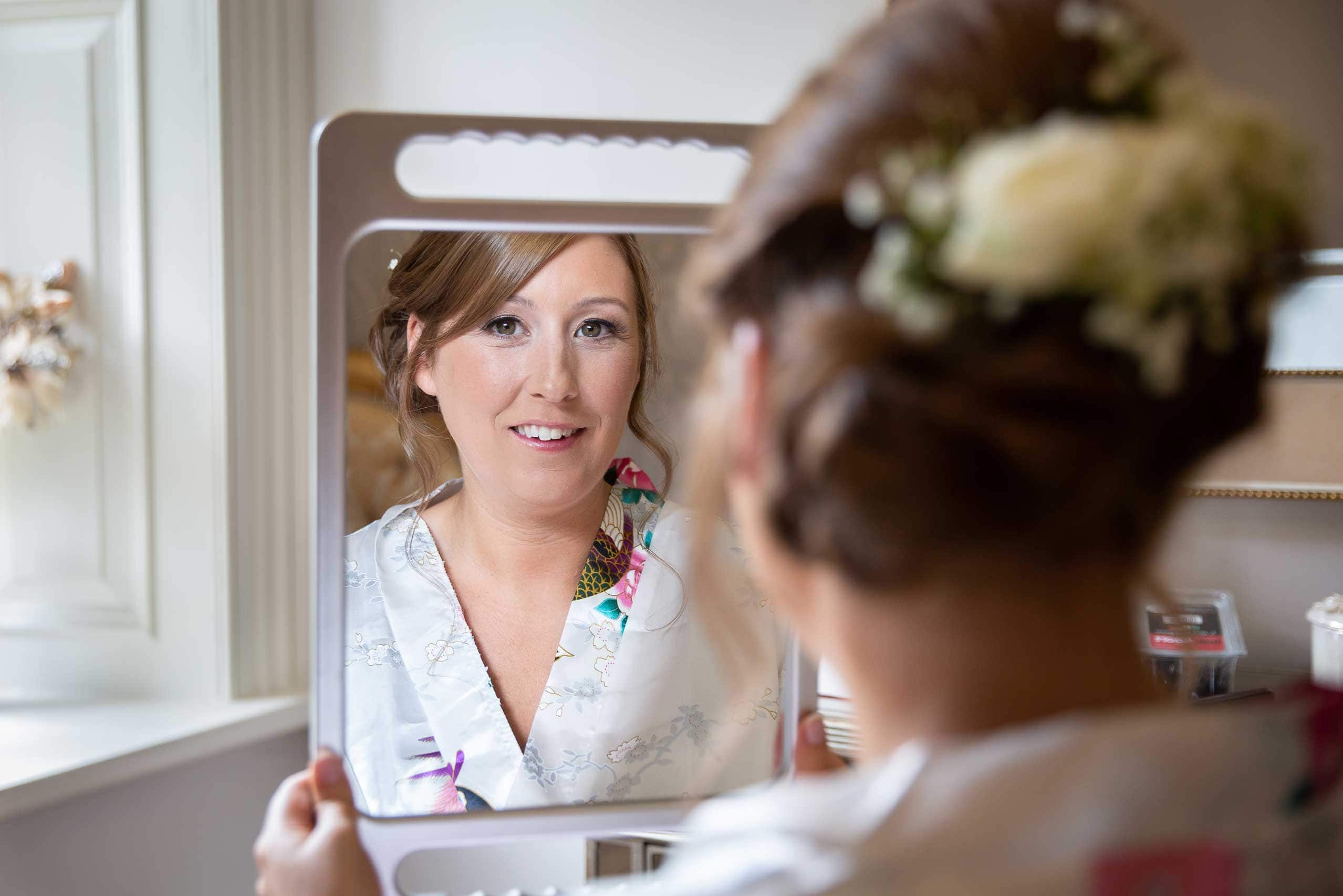 Bride looking in mirrow before wedding at Ellingham hall
