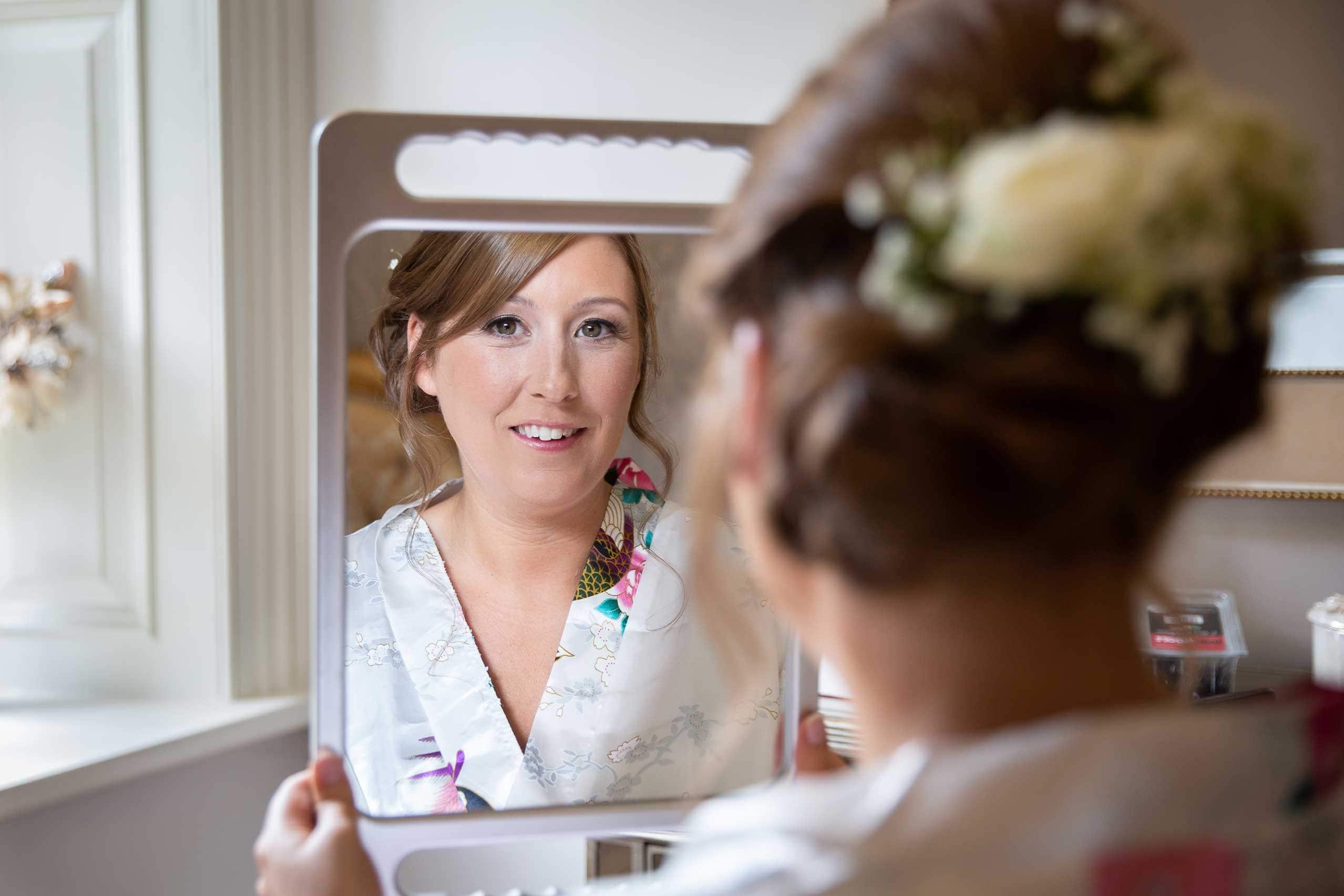 Bride looking in mirrow before wedding at Ellingham hall