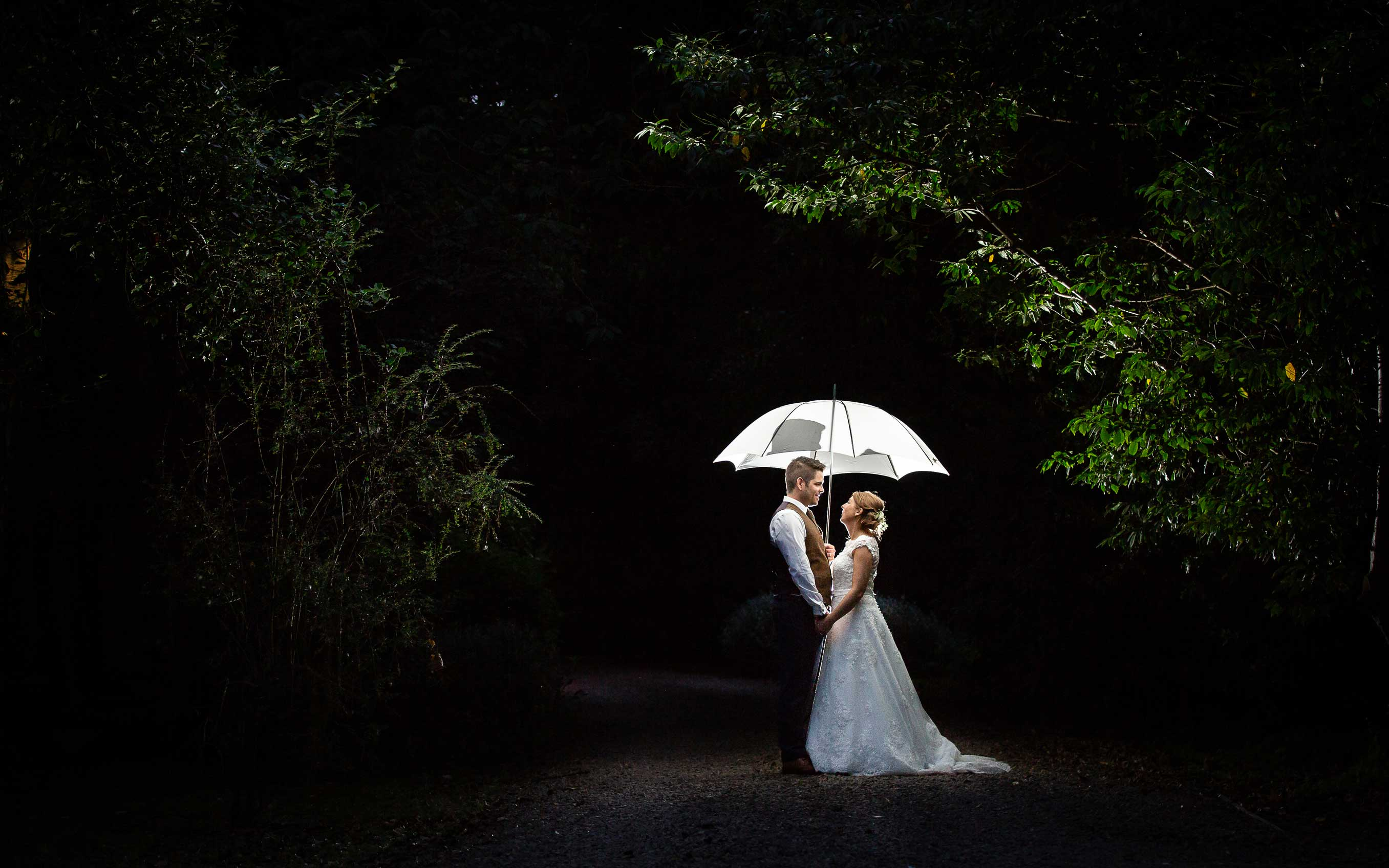 Bride and groom standing under brolly in the dark