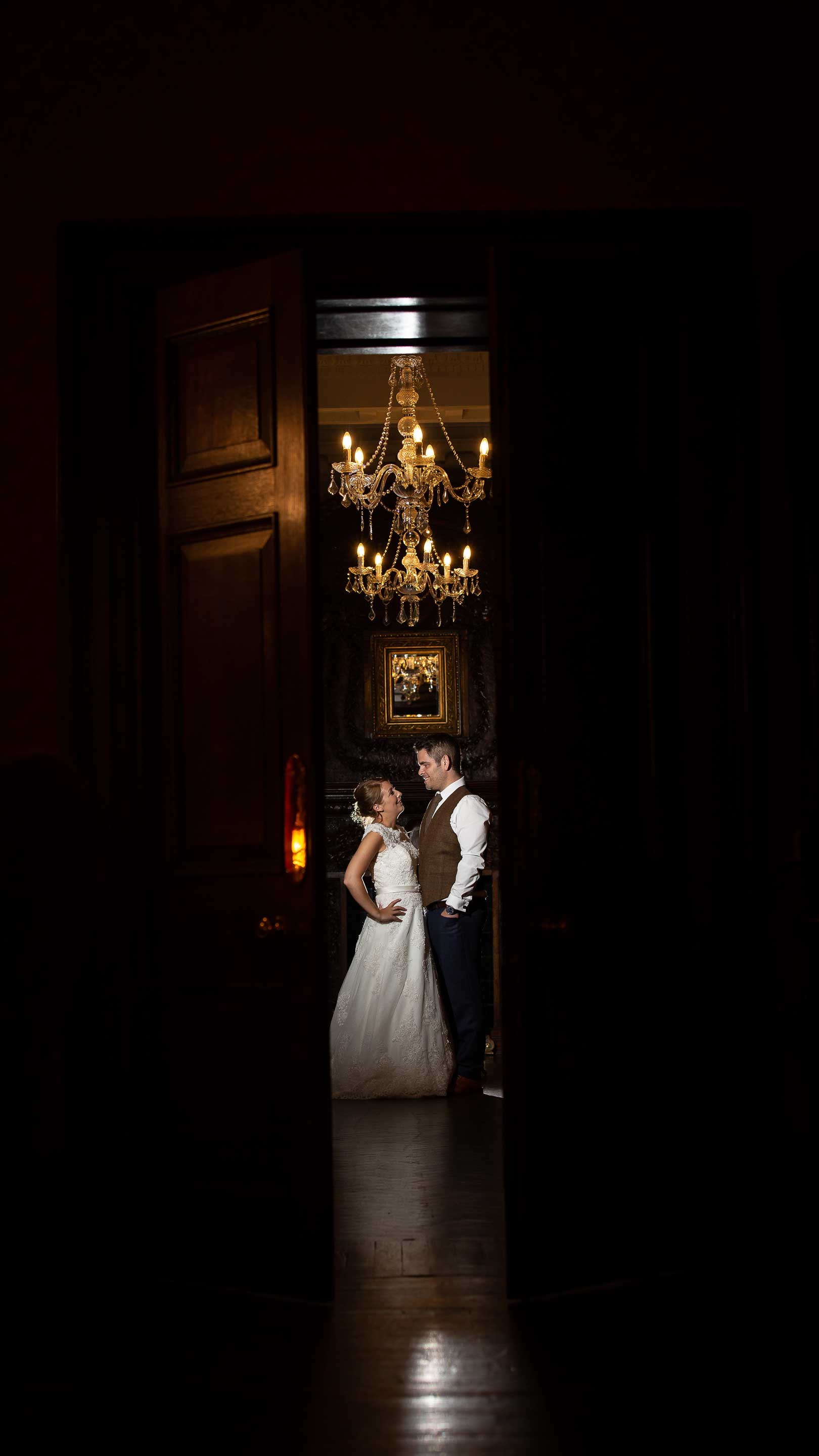 Photo of bride and groom in a dark groom lit by flash