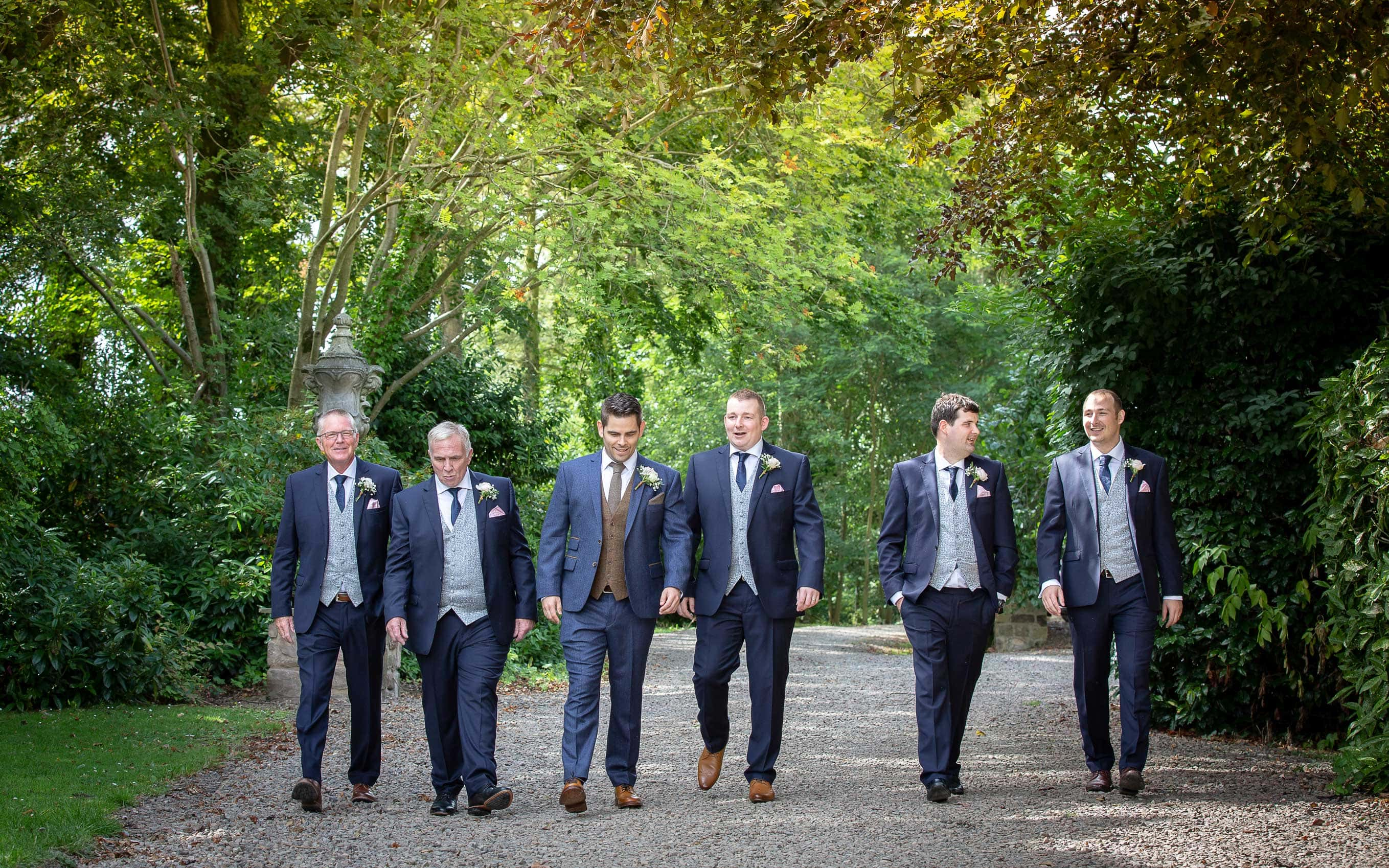 Photo of the groom and groomsmen walking to Ellingham Hall
