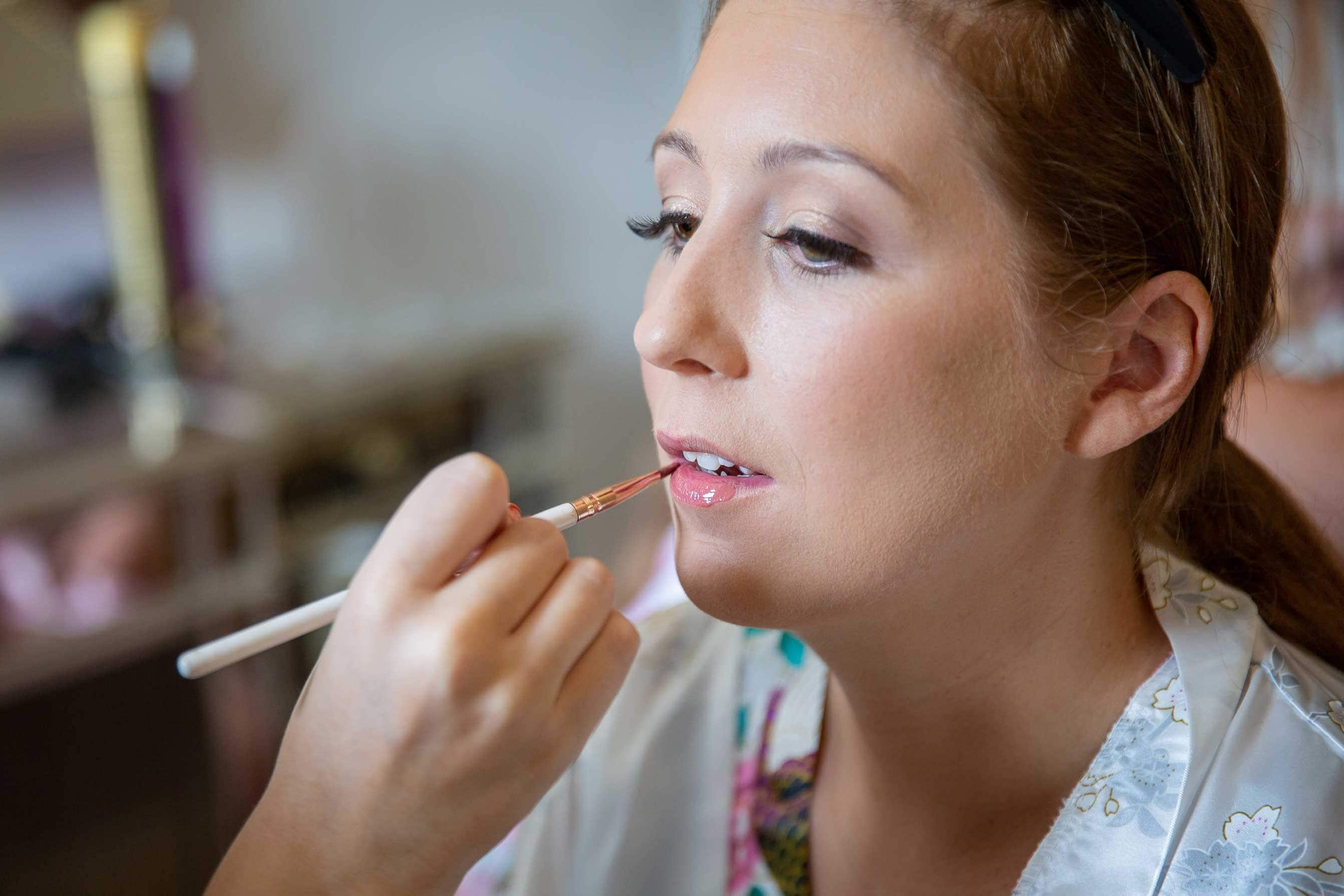bride getting having makeup done before wedding at Ellingham hall