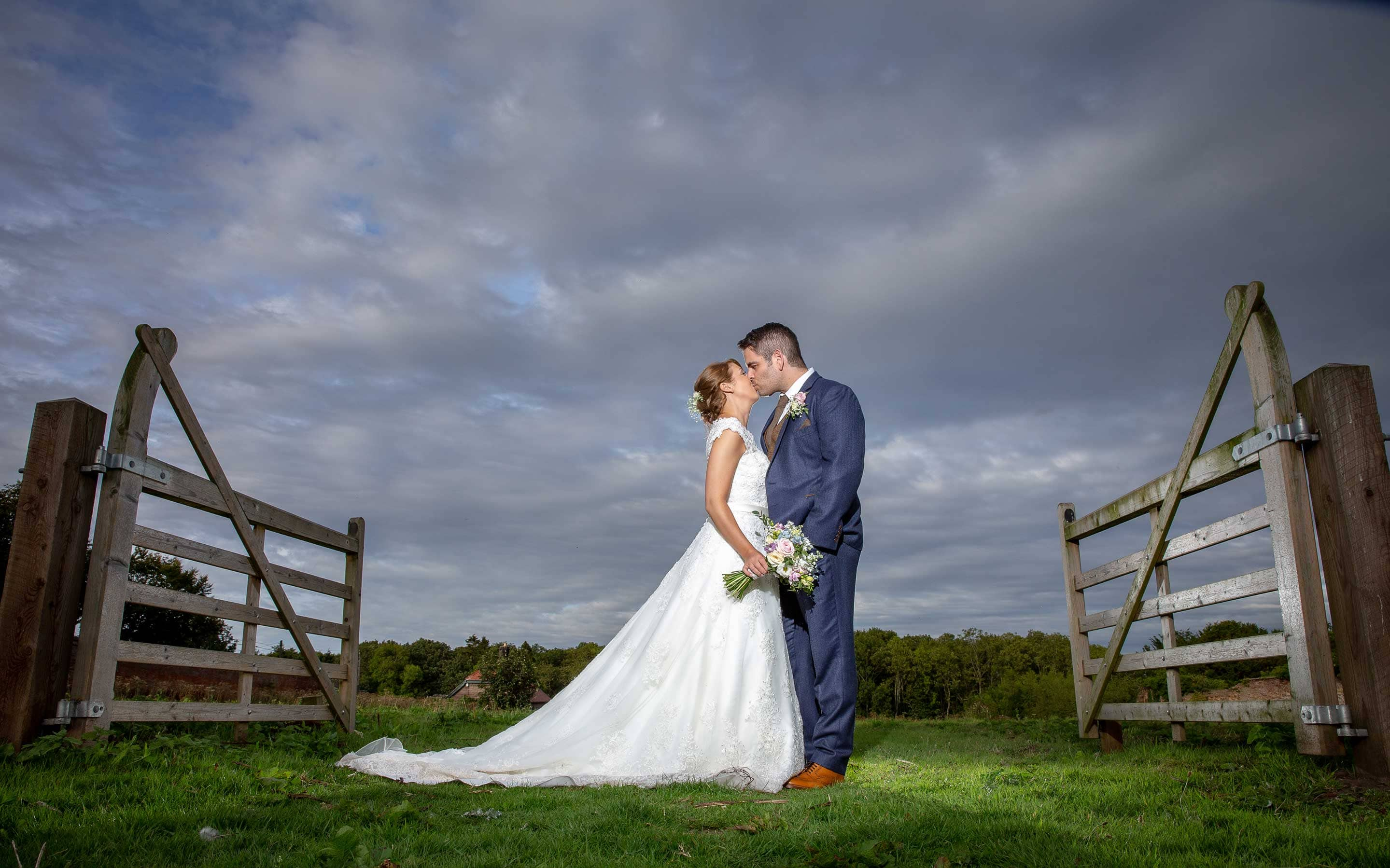 Wedding image of the bride and groom stood kissing near fence