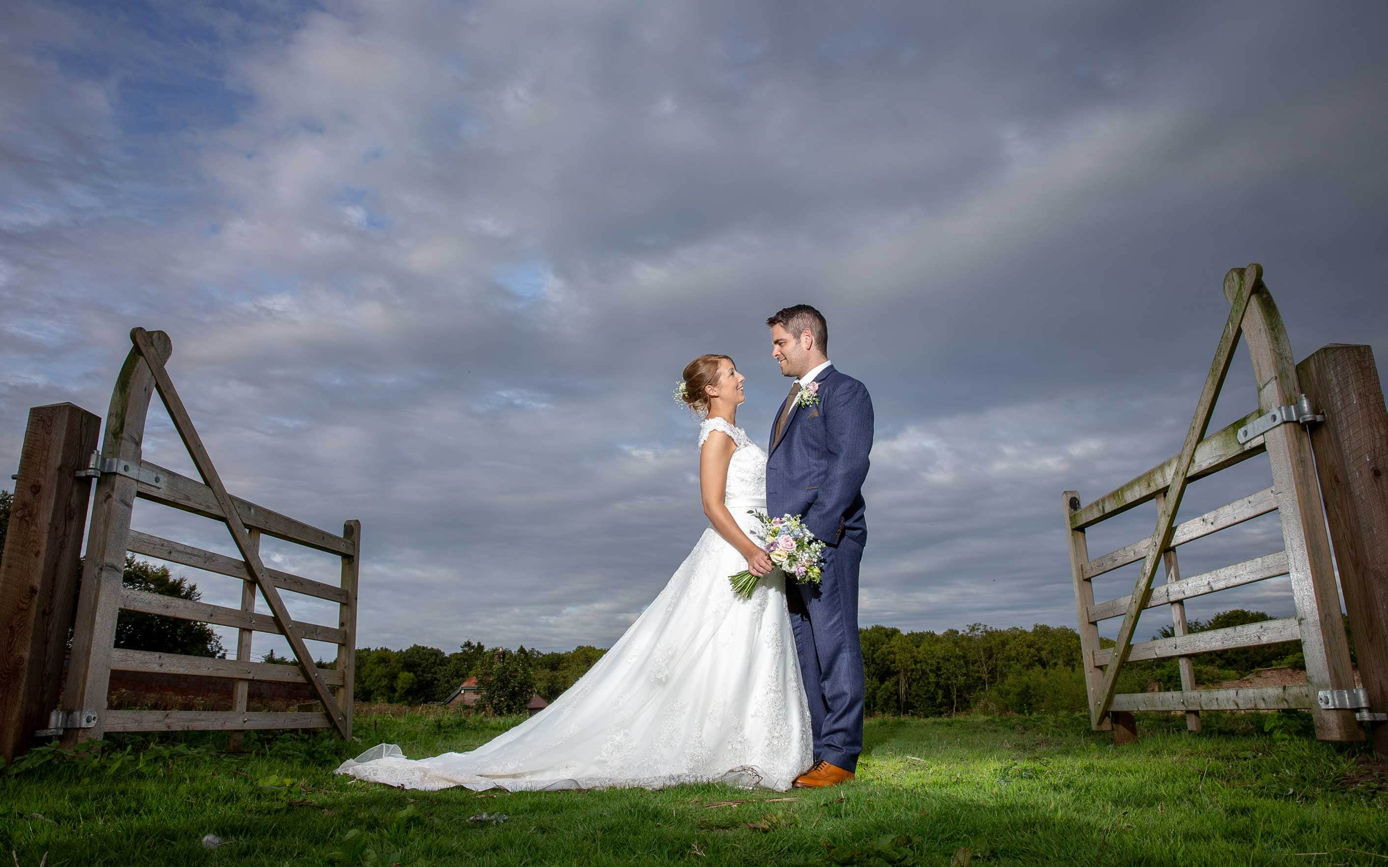 photo of the bride and groom near a fence