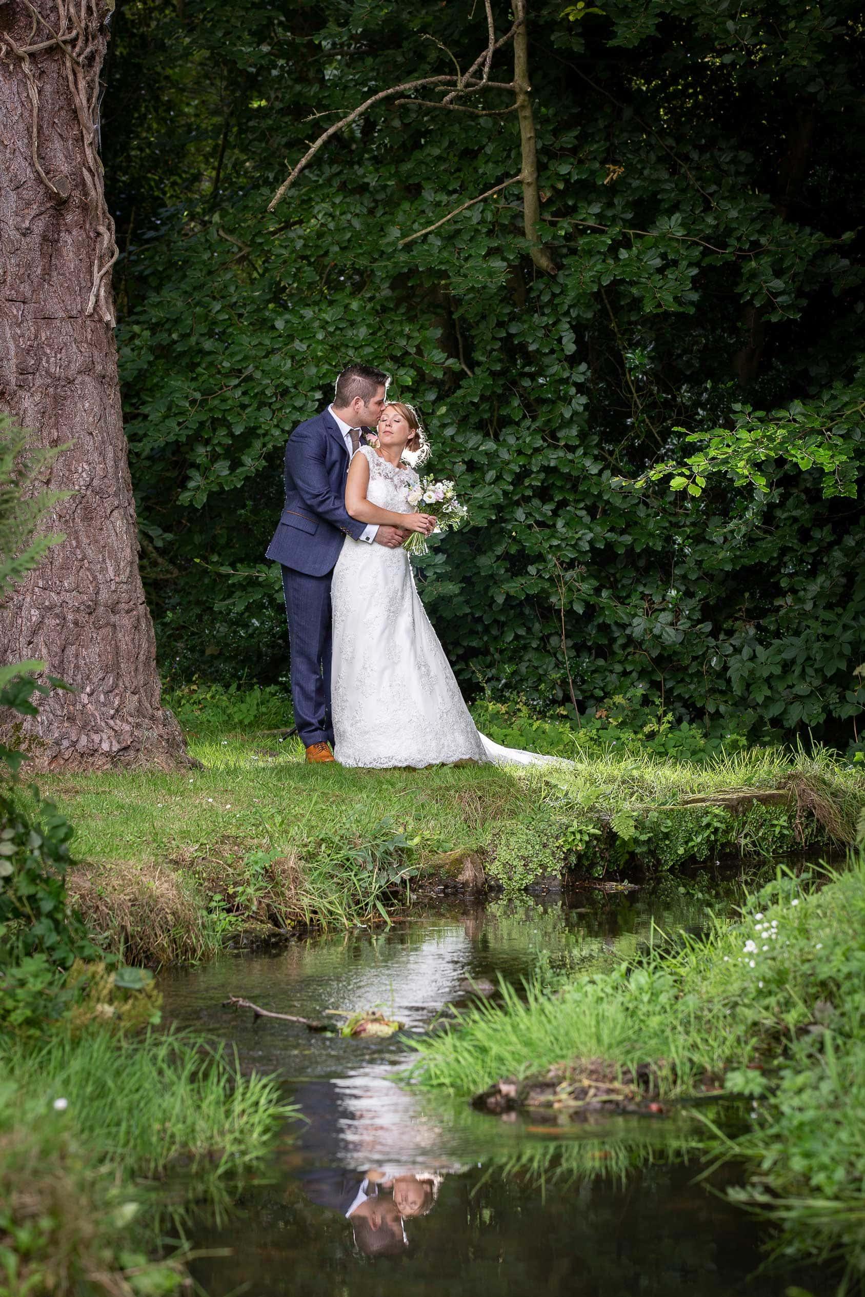 Photo of groom hugging bride near stream