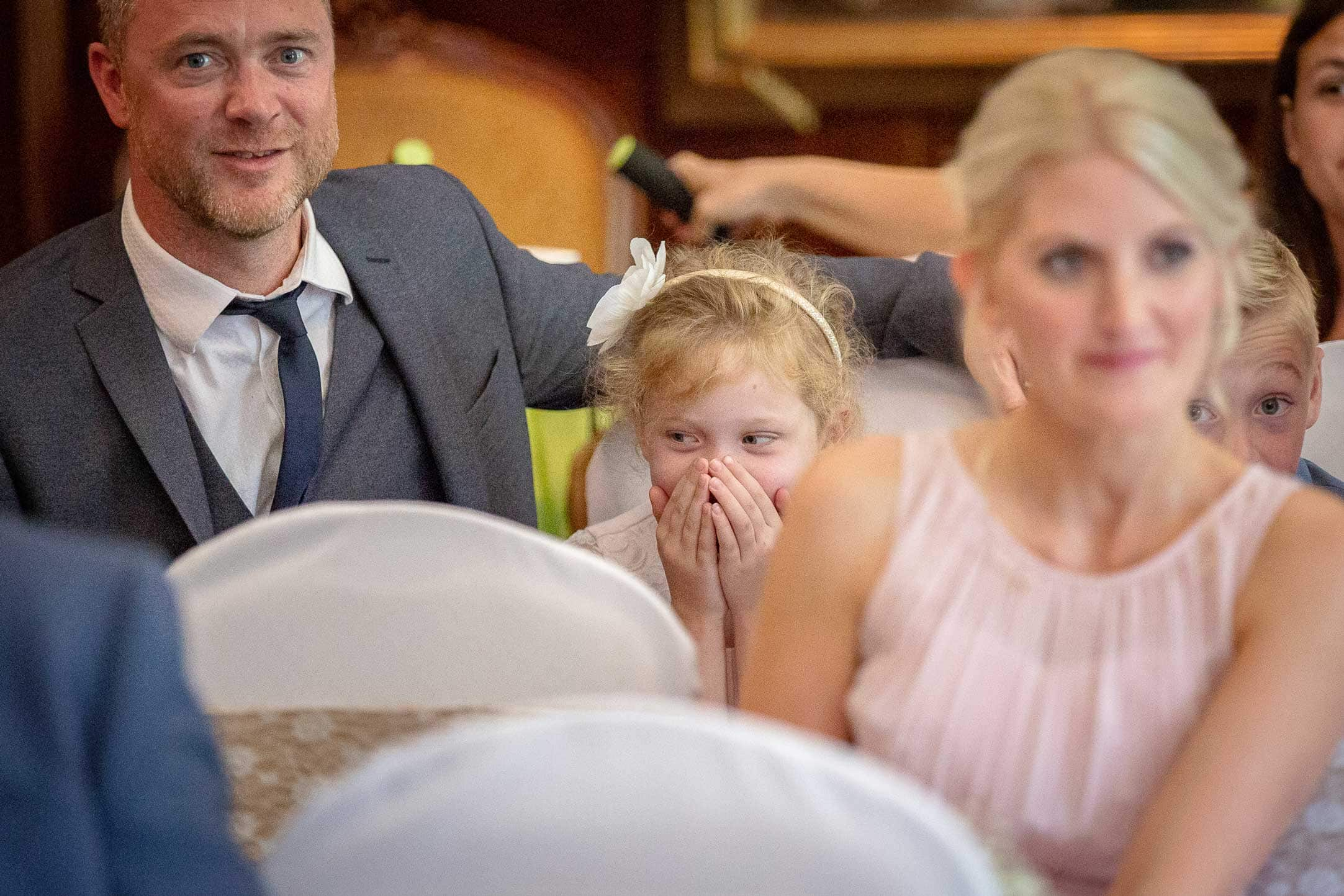 photo of a little girl laughing during a wedding ceremony at Ellingham hall