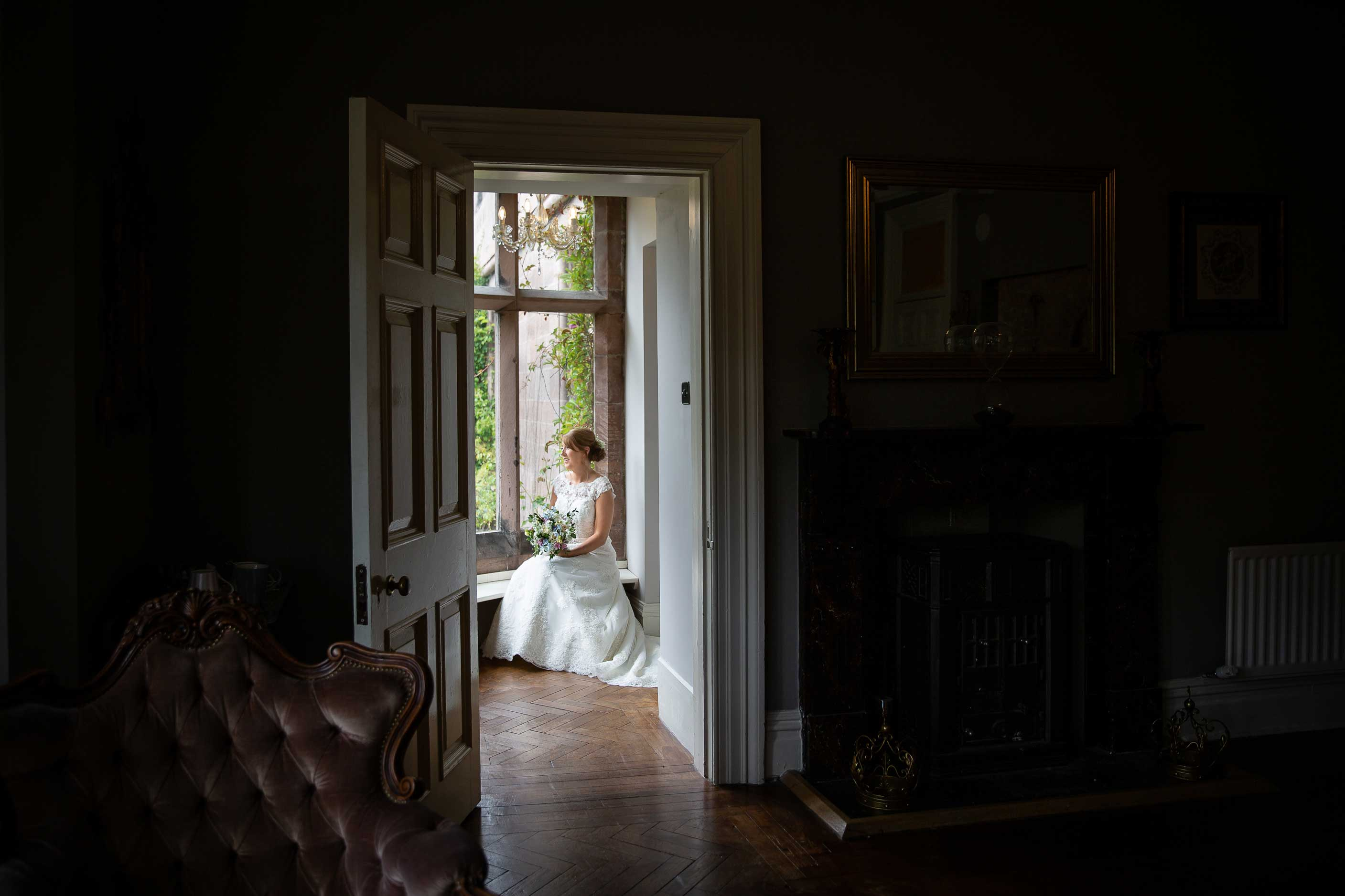 Bride sitting looking out of window at Ellingham hall