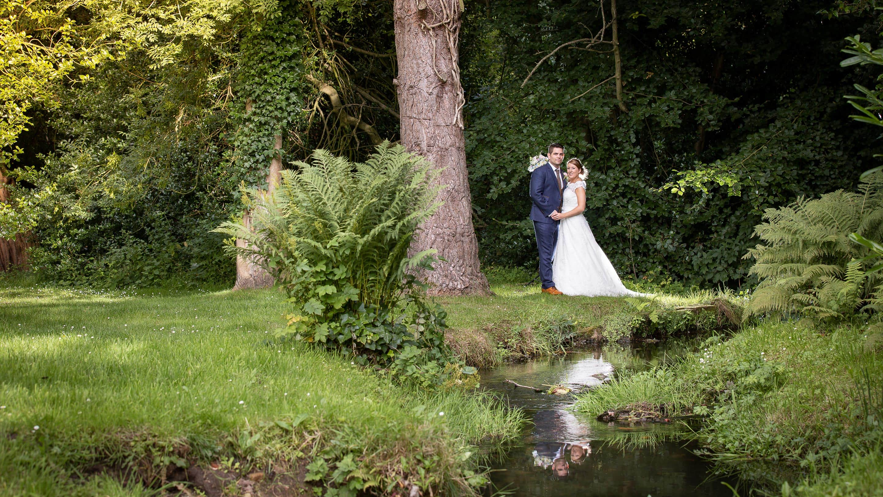Photo of bride and grrom near stream looking at camera