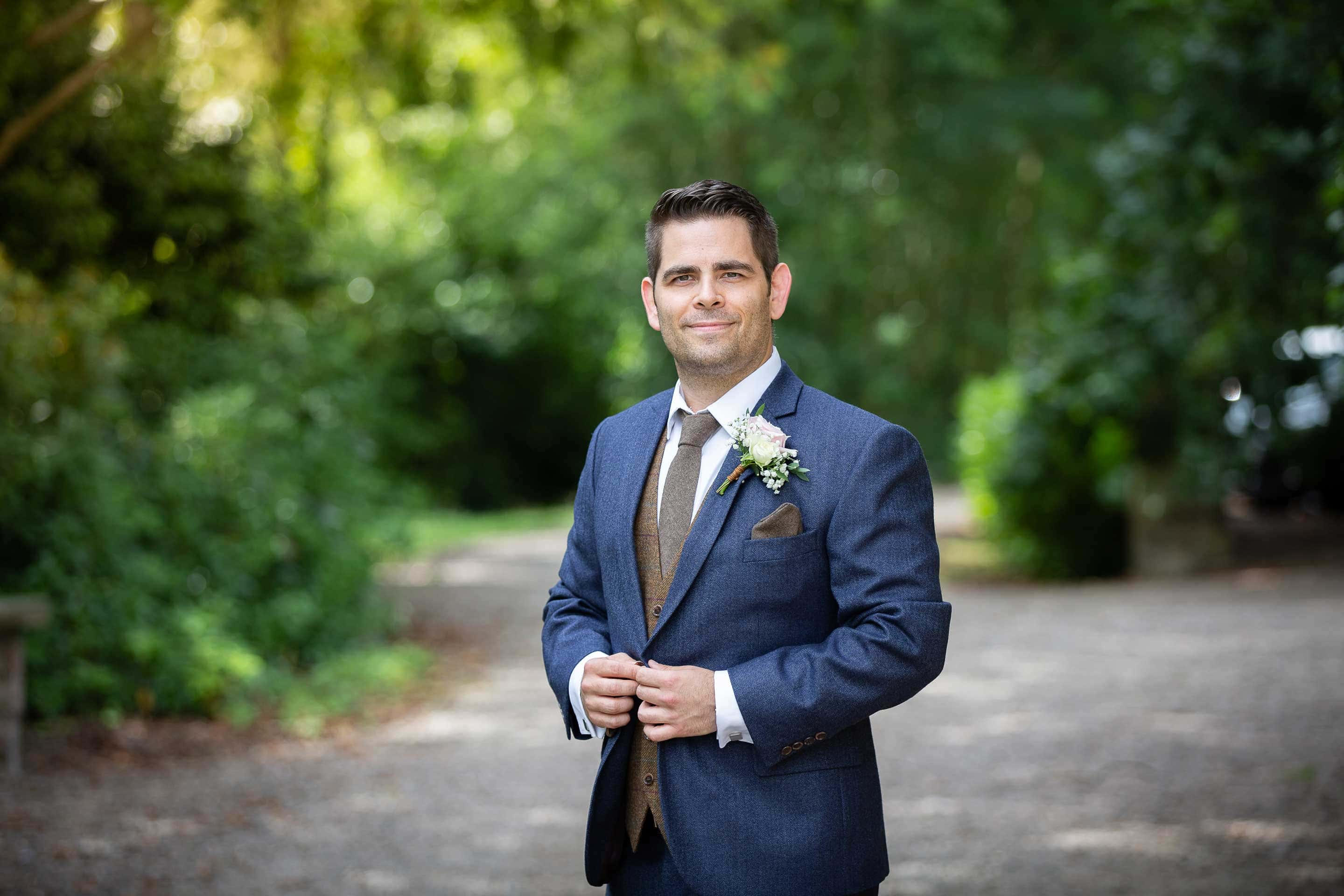 Groom standing outside of Ellingham hall before wedding