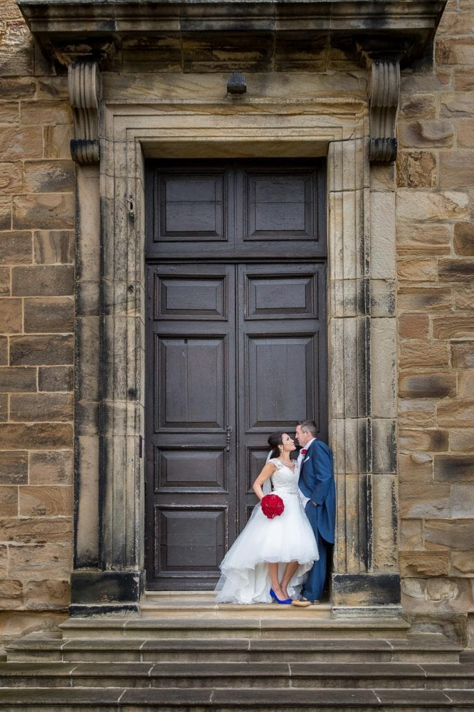 Wedding Couple standing in front of giant door at Lumley Castle