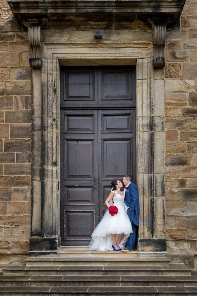 Wedding Couple standing in front of giant door at Lumley Castle