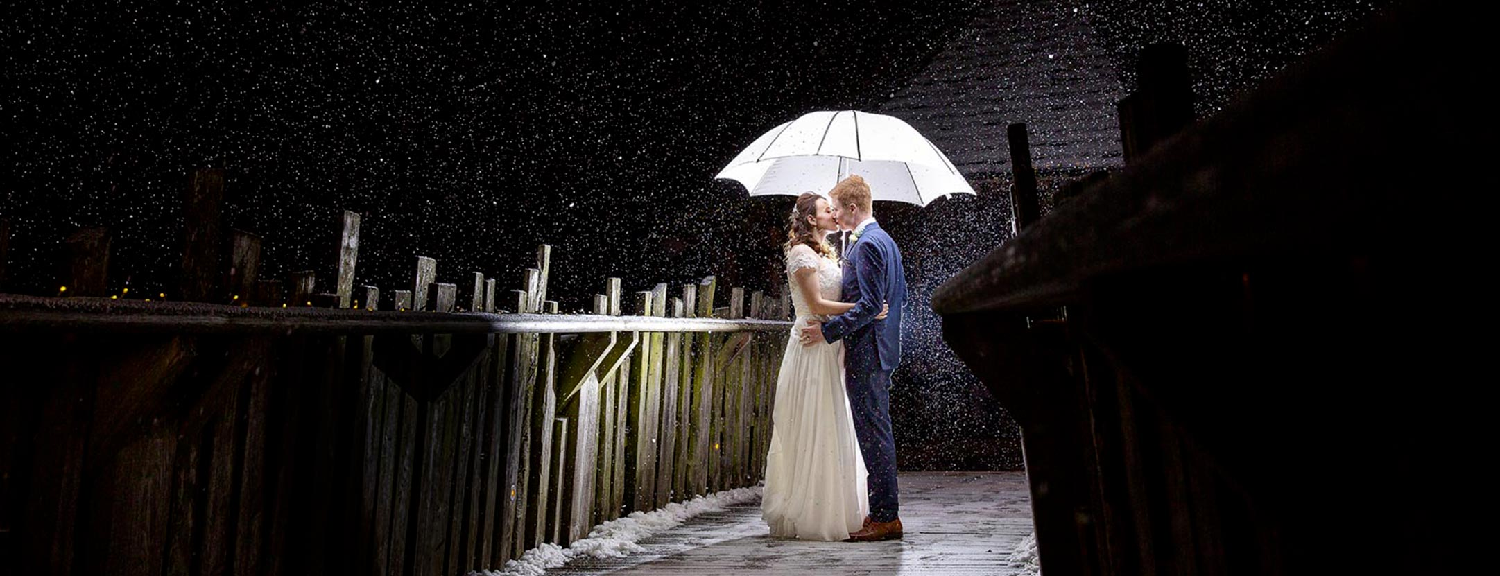 Wedding couple kissing under brolly while its snowing