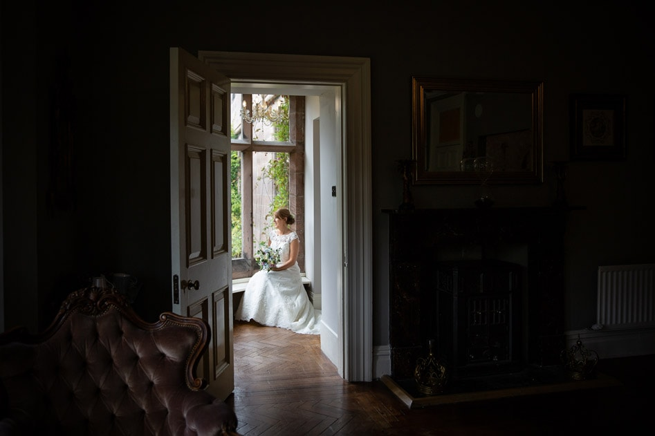 Bride looking out window at Ellingham Hall