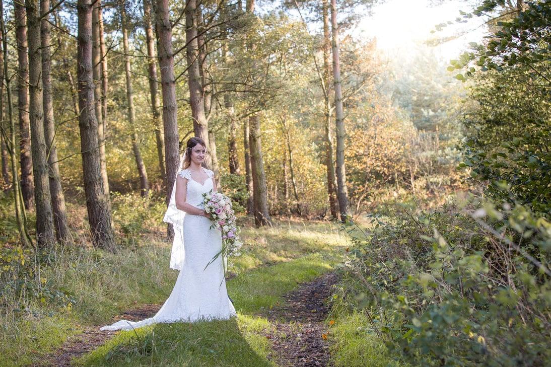 Bride standing in woods near Healey Barn