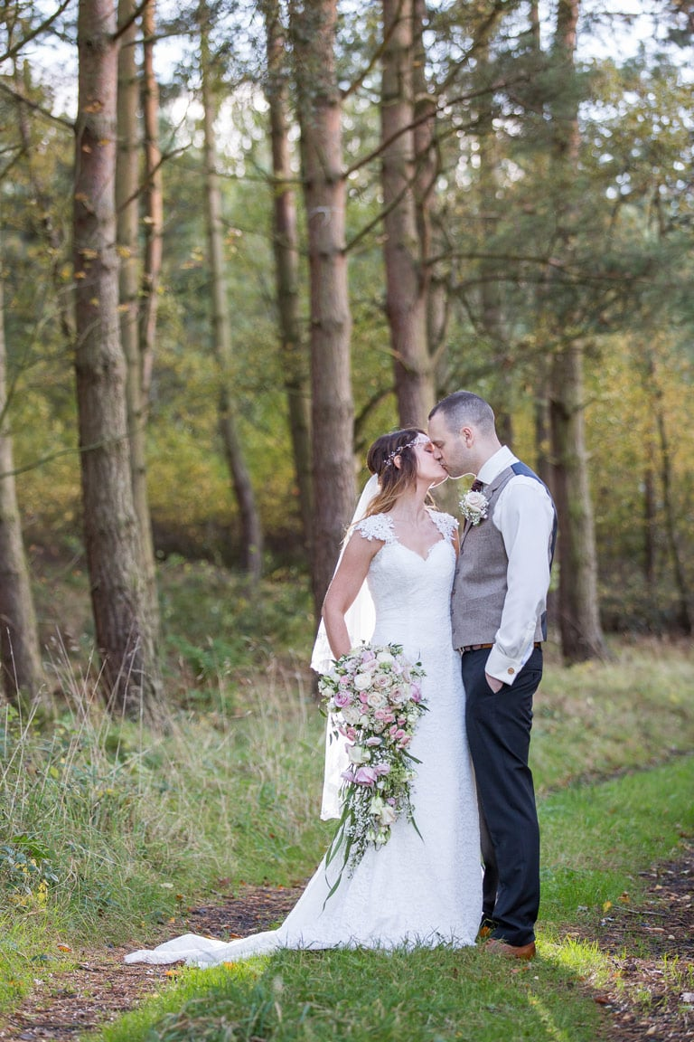 Bride and groom kissing in the woods at healey Barn