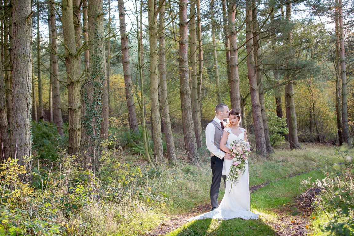 Bride and Groom standing in woods at Healey Barn