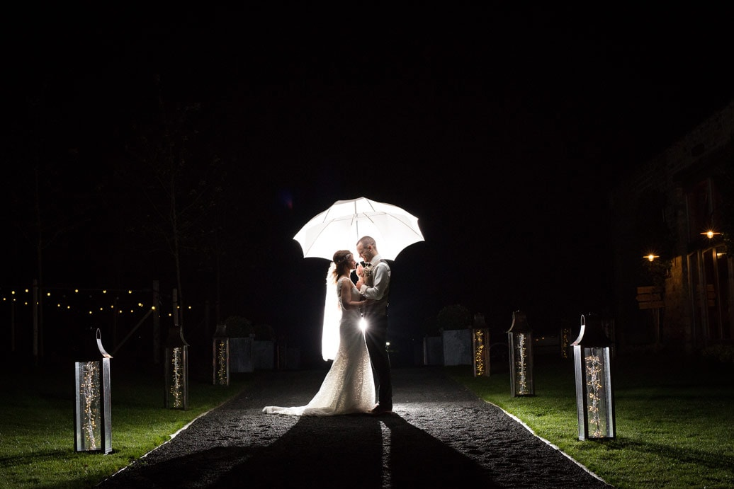 Photo of bride and groom with brolly at Healey Barn