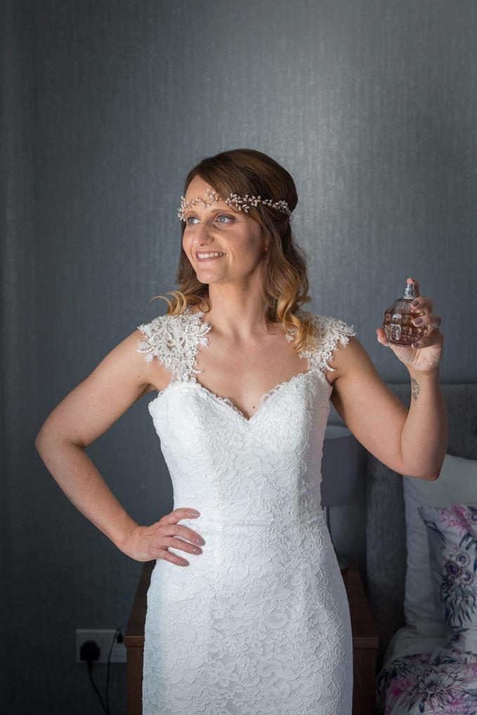 Bride spraying perfume at Healey Barn