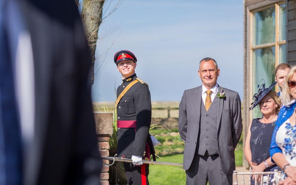 The groom looking at Bride walking down aisle