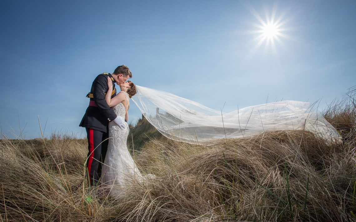 Photo of bride and groom kissing with veil blowing in wind