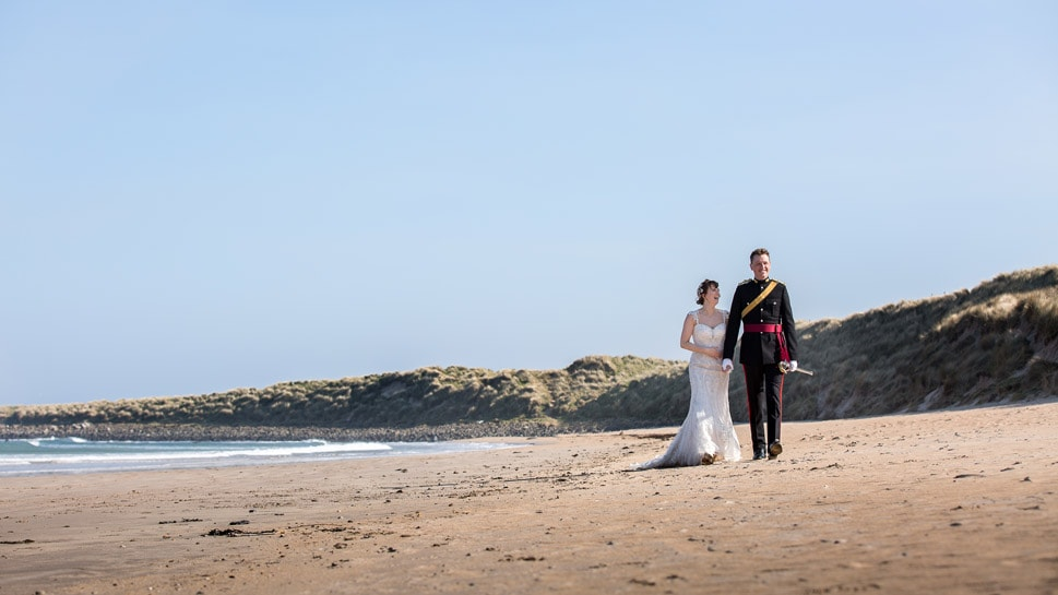 Bride and groom walking along a beach