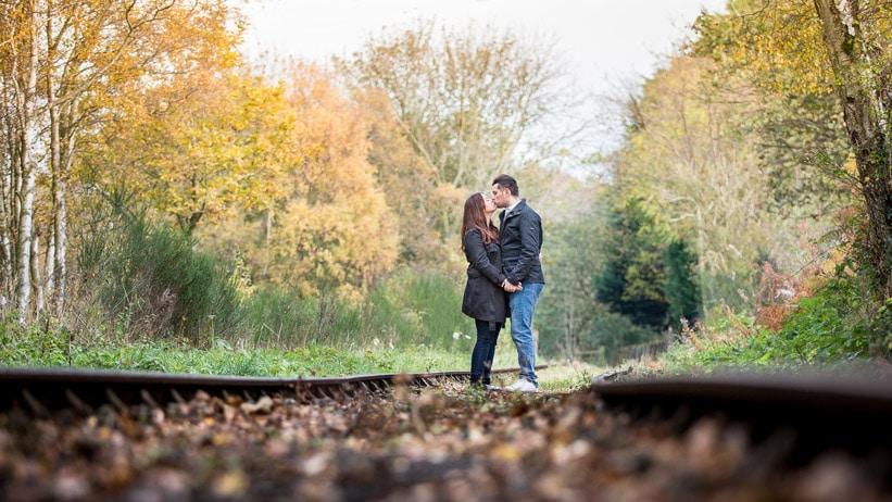 Couple kissing on train tracks during pre Wedding shoot