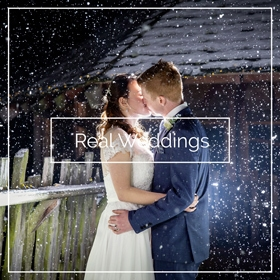 wedding couple kissing while snow is falling