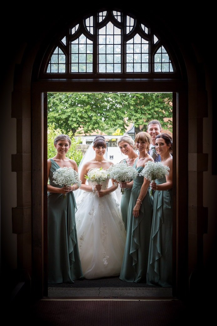 Photo of bride and bridesmaids waiting at church door