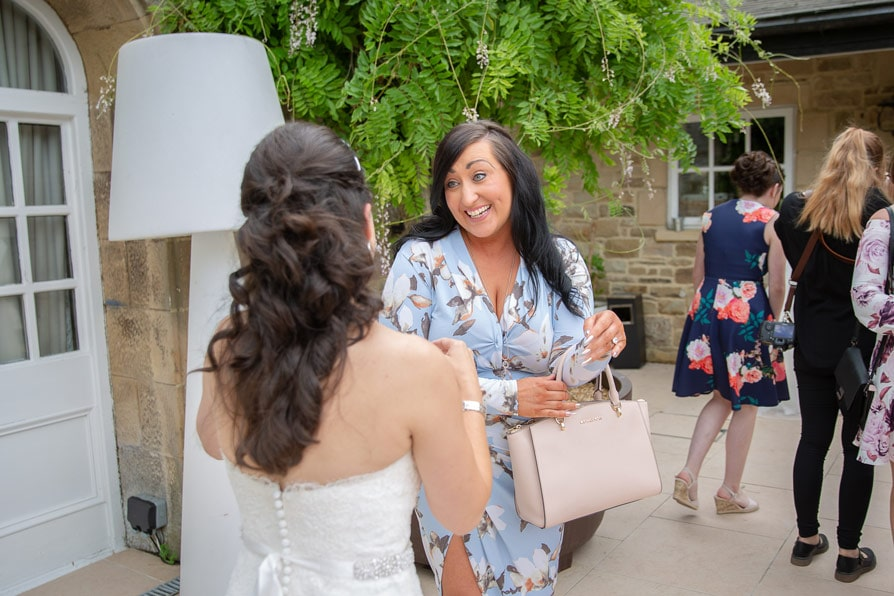 a wedding guest greeting bride at woodhill Hall