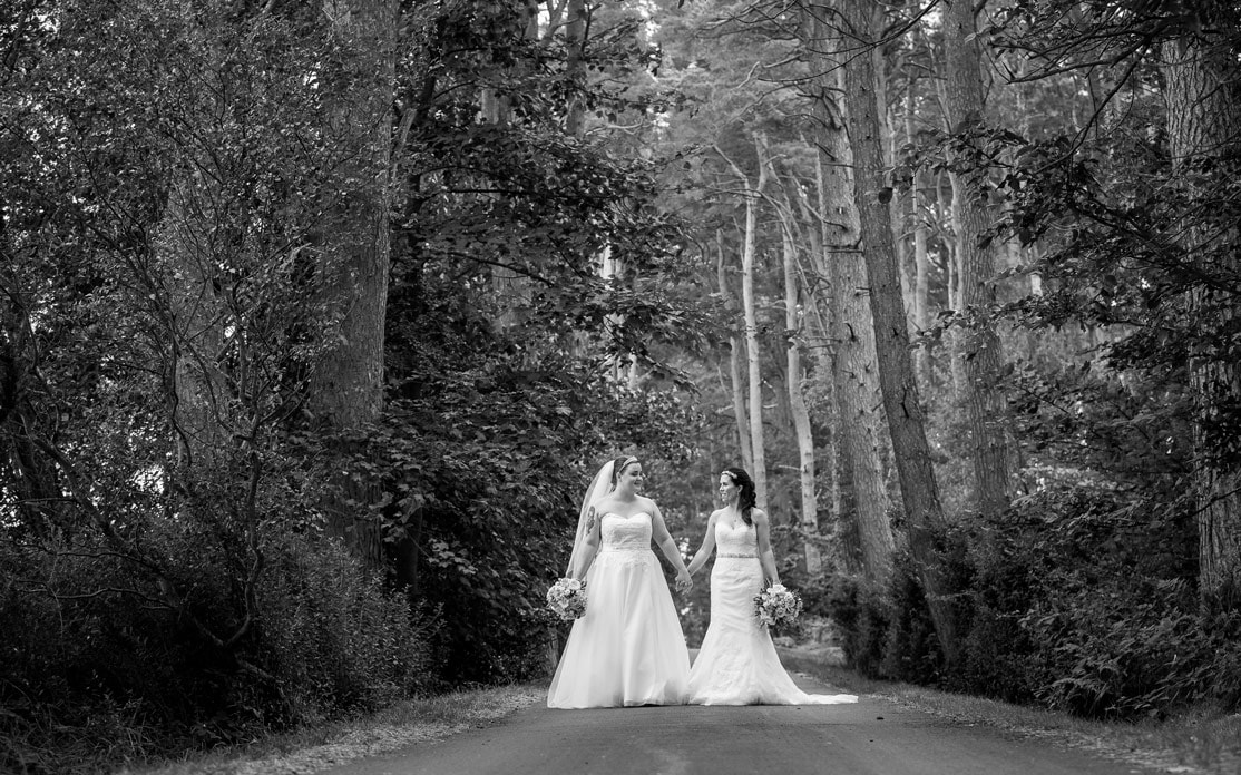 Black and white photo of brides walking in the woods