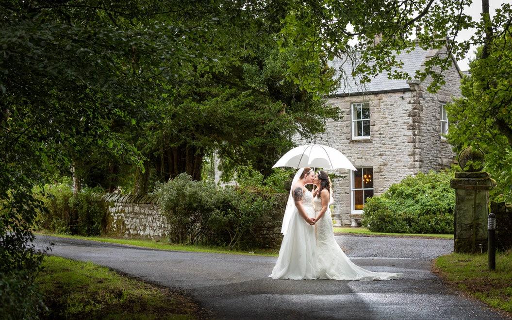 Brides kissing under brolly