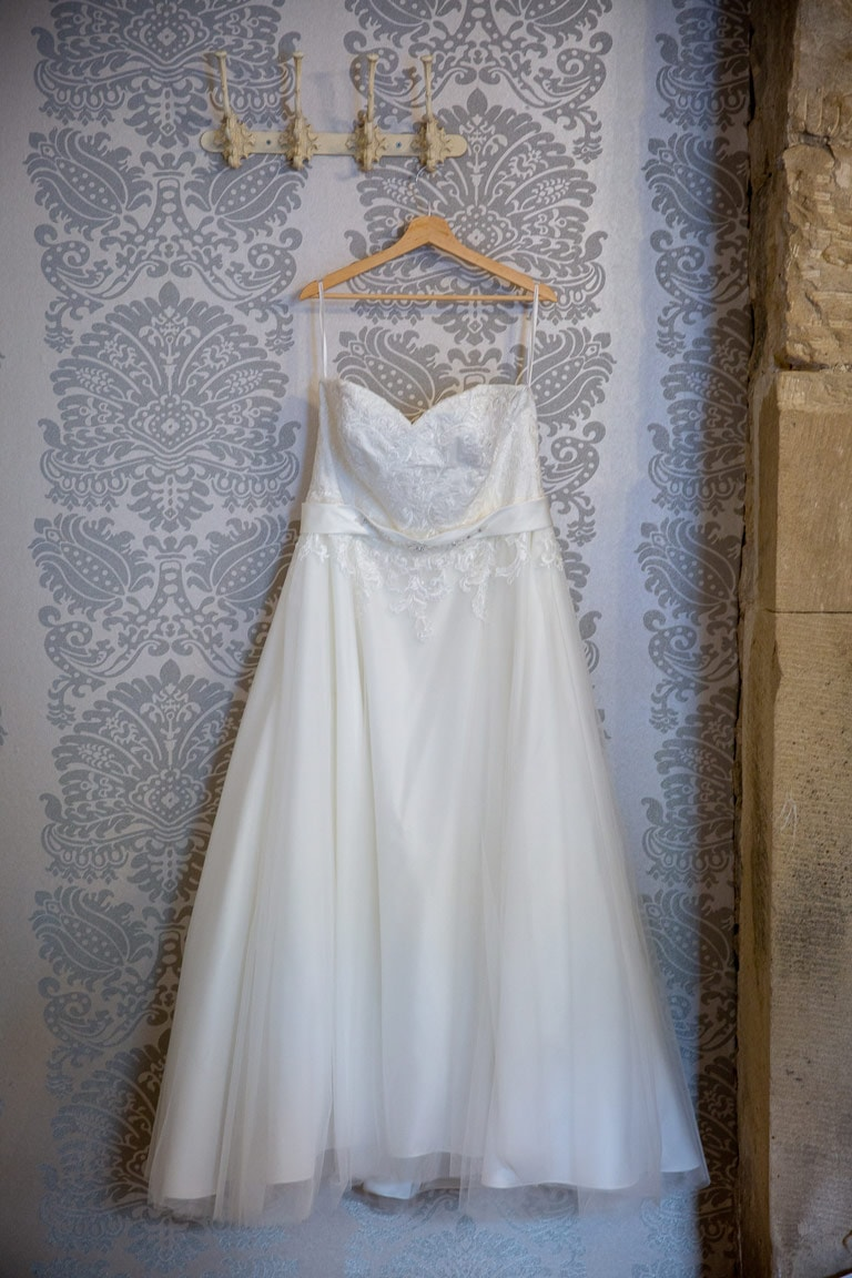 Photo of brides dress hanging up at Woodhill Hall