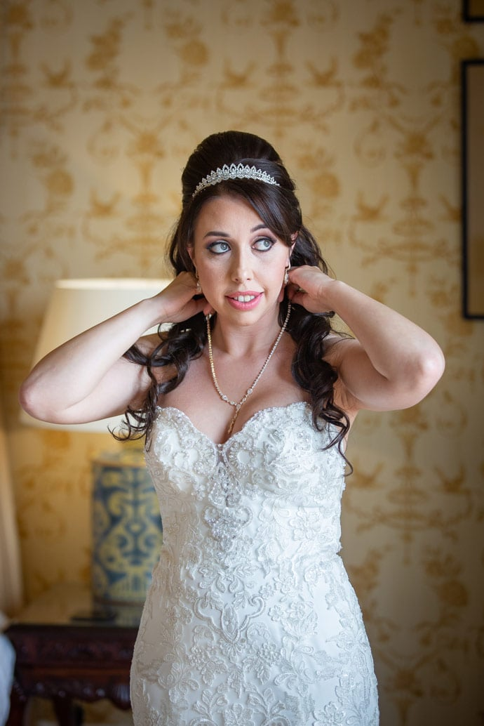 Bride putting on necklace at Wynyard Hall