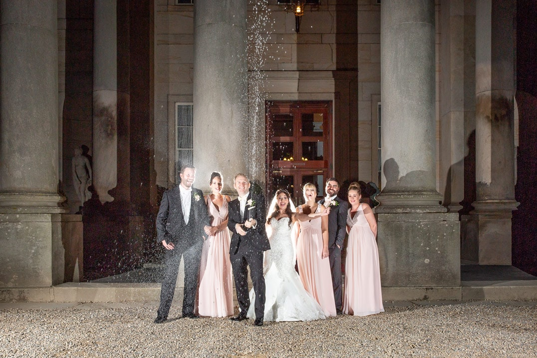 Photo of wedding party spraying champagne