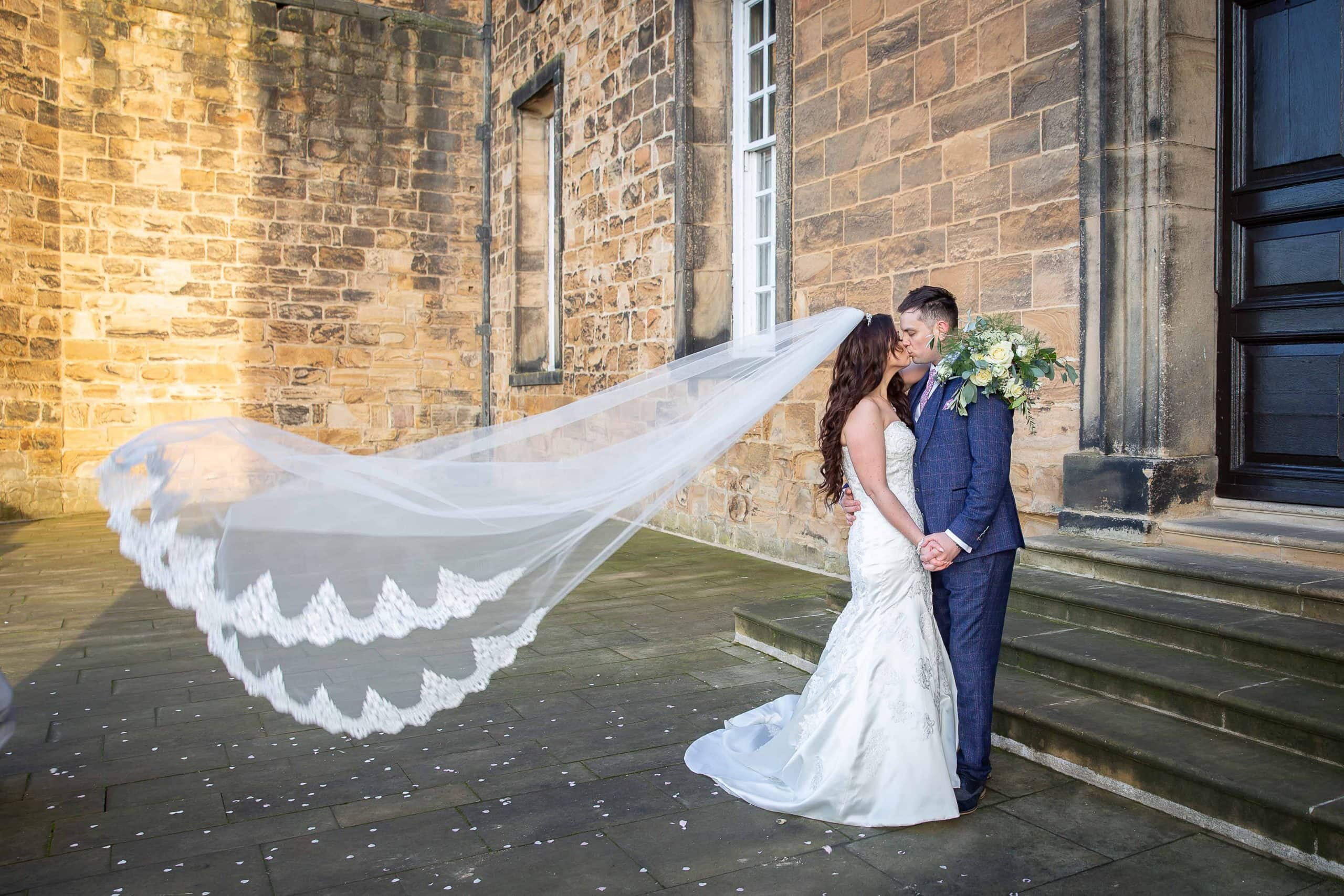 Bride and groom with veil blowing in wind